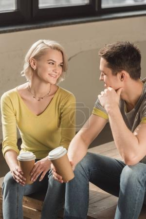 smiling couple sitting with disposable coffee cups at home