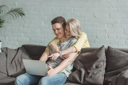 Photo for Smiling girlfriend hugging boyfriend and pointing on laptop - Royalty Free Image
