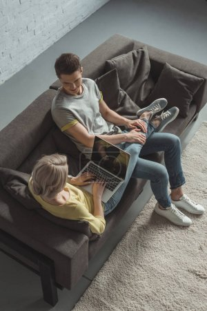 high angle view of couple sitting on sofa with laptop