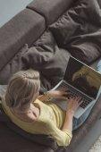 high angle view of girl using laptop on sofa