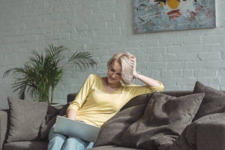 belle fille assise avec ordinateur portable sur le canapé