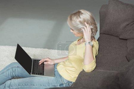 Photo pour Vue de côté de belle fille assise de plancher et à l'aide d'ordinateur portable - image libre de droit