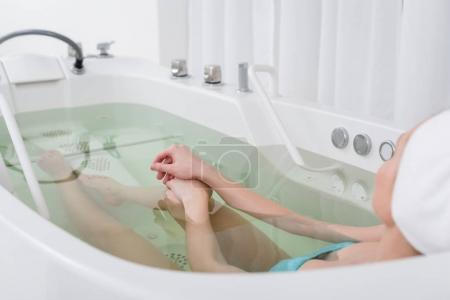 partial view of young woman with towel on head relaxing in bath in spa salon