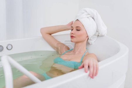 young woman in swimming suit with towel on head relaxing in bath in spa salon