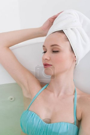 portrait of young woman with towel on head relaxing in bath in spa salon