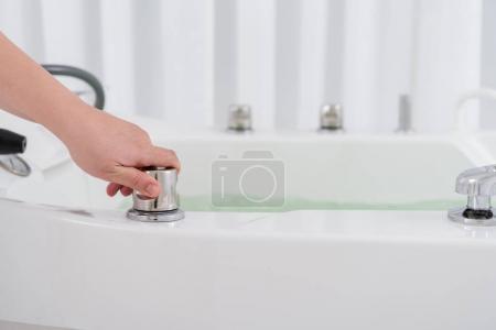 Photo pour Recadrée tir de régulation eau de spa salon adjoint en bain d'hydromassage - image libre de droit