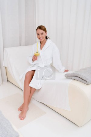 attractive young woman in white bathrobe with cocktail in spa salon