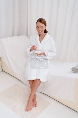smiling young woman in bathrobe with cup of tea in spa salon