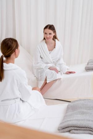 young women in white bathrobes having conversation in spa salon