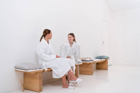 young women in white bathrobes in spa salon