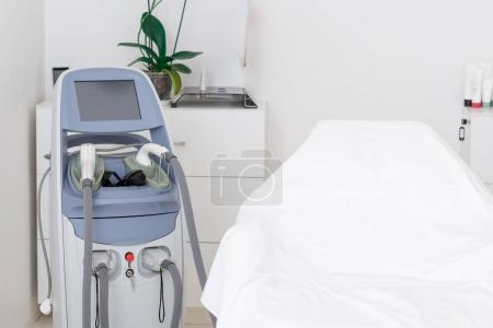 close up view of cosmetology apparatus and empty massage table in salon