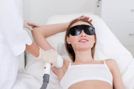 partial view of woman getting laser hair removal epilation on armpit in salon