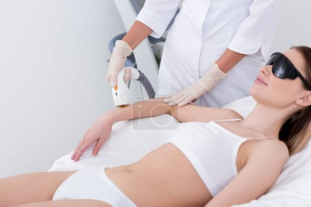 Photo for Cropped shot of woman getting laser hair removal procedure on arm in salon - Royalty Free Image