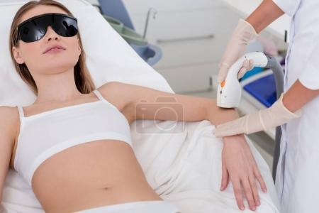 cropped shot of woman getting laser hair removal procedure on arm in salon