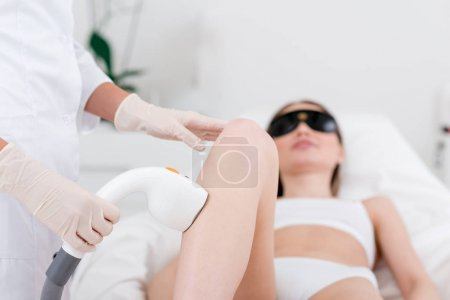 Photo for Partial view of woman receiving laser hair removal epilation on leg in salon - Royalty Free Image