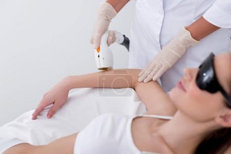 Photo pour Recadrée tir de femme se laser hair removal procédure sur bras au salon - image libre de droit