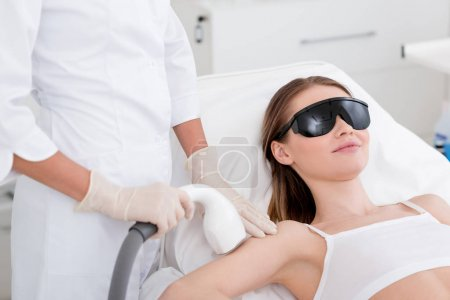partial view of woman receiving laser hair removal procedure on arm made by cosmetologist in salon