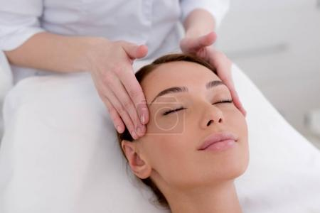 Photo pour Vue partielle de la jeune femme se faire masser la tête par un cosmétologue dans le salon - image libre de droit