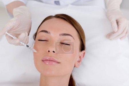 Photo pour Vue partielle de la jeune femme obtenant injection de beauté faite par le cosmétologue dans le salon - image libre de droit