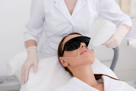 Photo for Partial view of young woman receiving laser hair removal epilation on face in salon - Royalty Free Image