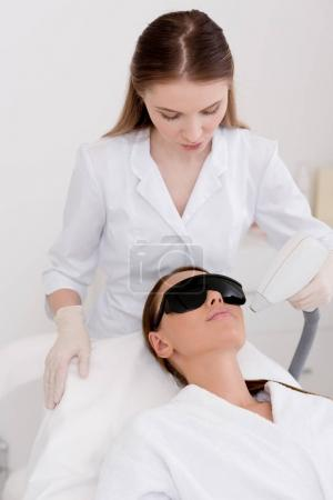 Photo for Young woman getting laser hair removal procedure on face in salon - Royalty Free Image
