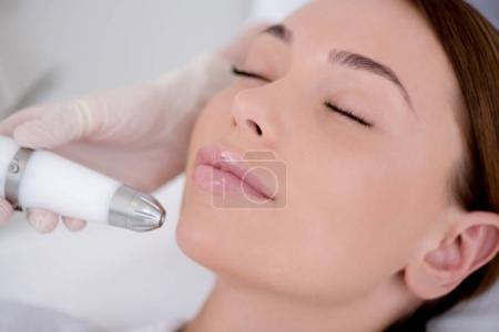 Photo pour Vue partielle de la femme recevant un traitement facial dans le salon de cosmétologie - image libre de droit