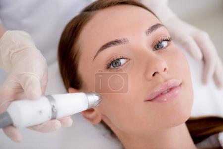 Photo pour Vue partielle de la femme à obtenir un traitement du visage au salon de cosmétologie - image libre de droit