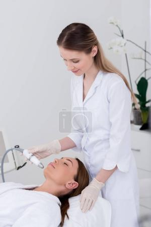 young woman getting facial treatment in cosmetology salon