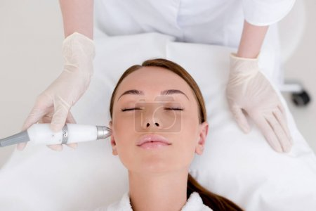 partial view of woman getting facial treatment in cosmetology salon