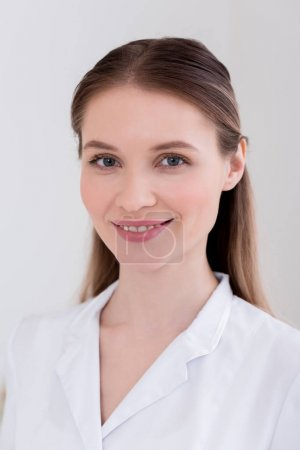 portrait of smiling cosmetologist in white coat in salon