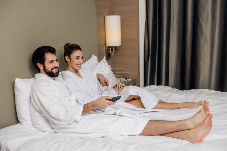 beautiful couple in bathrobes with remote control relaxing in bed at hotel suite and watching tv