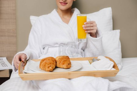cropped shot of woman in bathrobe relaxing at hotel room with breakfast in bed