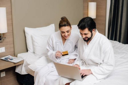 happy couple in bathrobes making e-shopping with laptop and credit card at hotel suite
