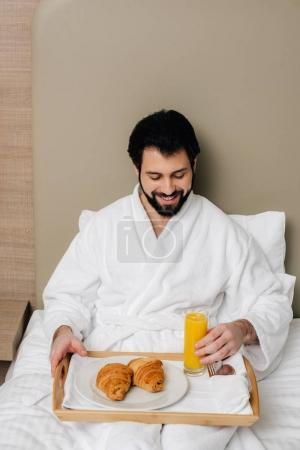 happy man in bathrobe with food on tray sitting on bed at hotel suite