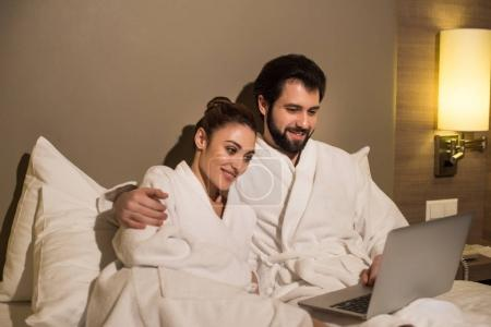 beautiful couple in bathrobes using laptop together in bed of hotel suite