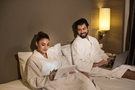 smiling couple in bathrobes using devices in bed of hotel suite