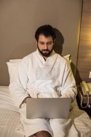 handsome man in bathrobe using laptop in bed at hotel suite in evening