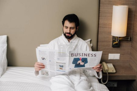 happy businessman in bathrobe reading newspaper while relaxing on bed at hotel suite