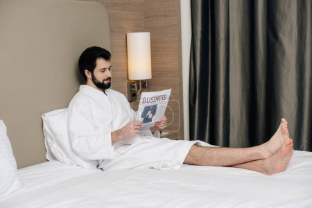 smiling businessman in bathrobe reading newspaper while relaxing on bed at hotel suite