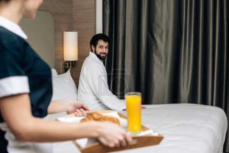 cropped shot of maid in uniform holding tray with croissants and juice for hotel guest while he sitting on bed