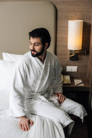 smiling man in bathrobe sitting on bed at hotel suite