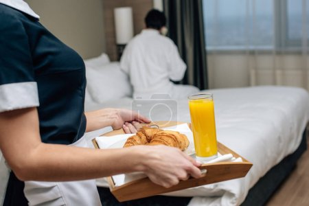 cropped shot of maid in uniform holding tray with croissants and juice for hotel guest
