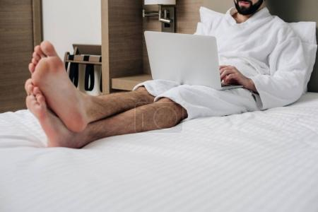 handsome man in bathrobe using laptop in bed at hotel suite