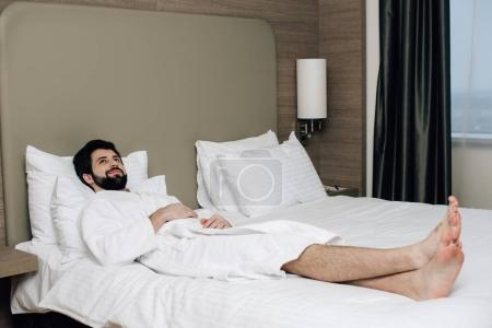 handsome man in bathrobe relaxing on bed at hotel suite