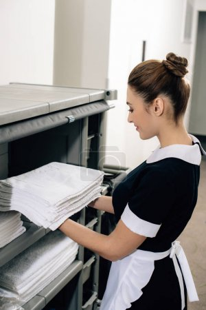 young attractive maid in uniform taking towels from shelf of housekeeping cart