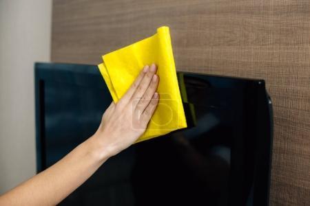 abgeschnittene Aufnahme von Dienstmädchen in Uniform, die TV-Bildschirm mit Lappen säubern
