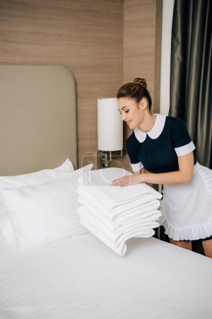 Photo for Happy maid in uniform putting stack of clean towel on bed at hotel suit - Royalty Free Image