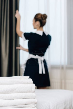 young maid in uniform shutting curtain with stack of clean towels standing on foreground