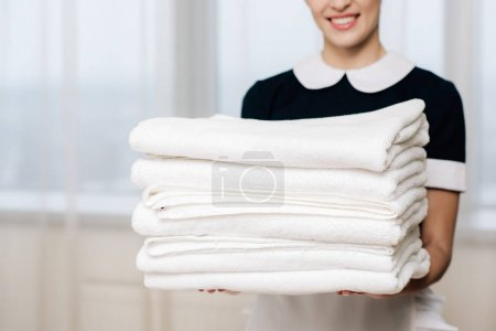 cropped shot of smiling maid in uniform holding stack of clean towels