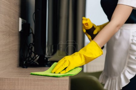 Photo for Cropped shot of maid in uniform wiping shelf with rag and aerosol furniture cleaner - Royalty Free Image